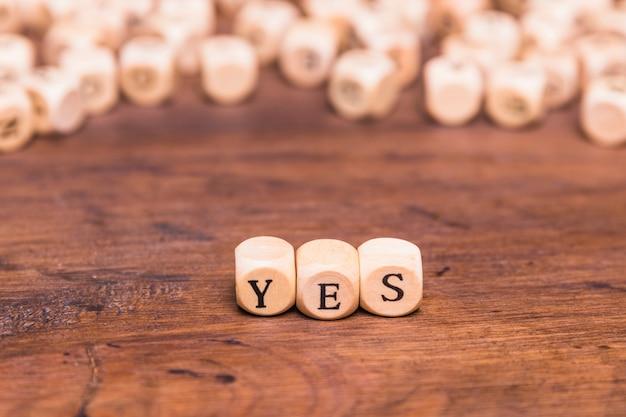 Palavra sim em blocos de madeira Foto gratuita