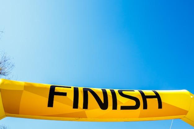 Palavra terminar em uma bandeira amarela contra um céu azul. Foto Premium