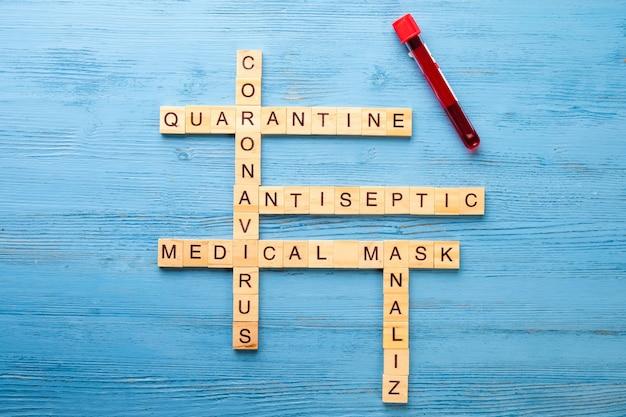 Palavras cruzadas sobre um tema médico em uma mesa de madeira. conceito de quarentena pandêmica Foto Premium