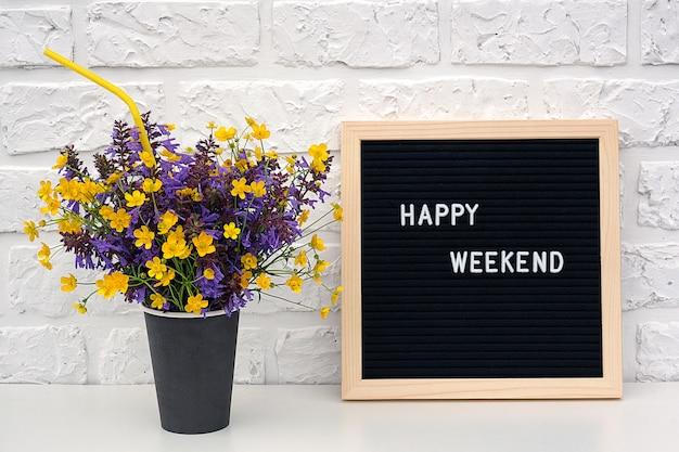 Palavras de feliz fim de semana no quadro de cartas preto e buquê de flores amarelas de leão Foto Premium