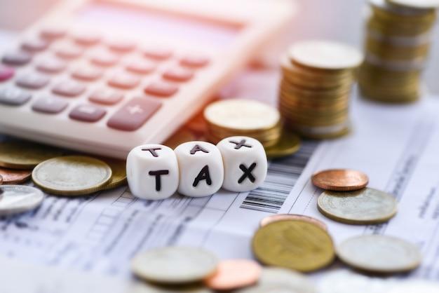 Palavras de impostos e moedas empilhadas calculadora em papel de bill fatura para preenchimento de imposto de tempo Foto Premium