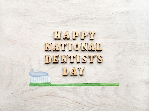Palavras do dia do dentista com escova de dentes na mesa de madeira Foto Premium