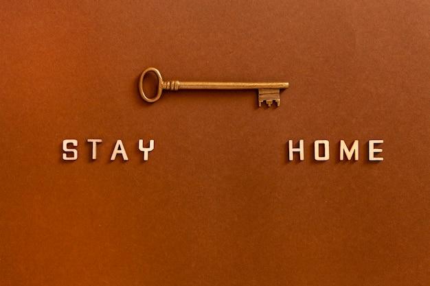 Palavras, ficar em casa, feito de letras de madeira e chave, conceito de auto-quarentena em casa como medida preventiva contra o vírus da corona covid 19 fundo de surto Foto Premium