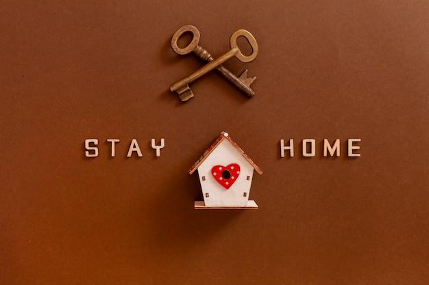 Palavras fique em casa feito de letras de madeira, figuras de casa e chaves, conceito de quarentena em casa como medida preventiva contra o surto de vírus de coroa covid19. Foto Premium