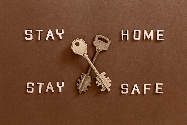 Palavras fique em casa fique seguro, feito de letras de madeira e duas chaves, o conceito de quarentena em casa como medida preventiva contra o surto de vírus corona covid 19. Foto Premium