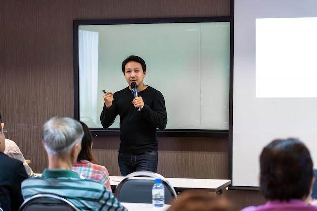Palestrante asiático ou palestra com terno casual no palco em frente à apresentação da sala Foto Premium
