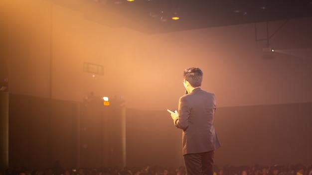 Palestrante no palco e falar sobre negócios em sala de seminários Foto Premium