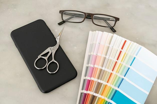 Paleta de cores com óculos em posição plana Foto gratuita