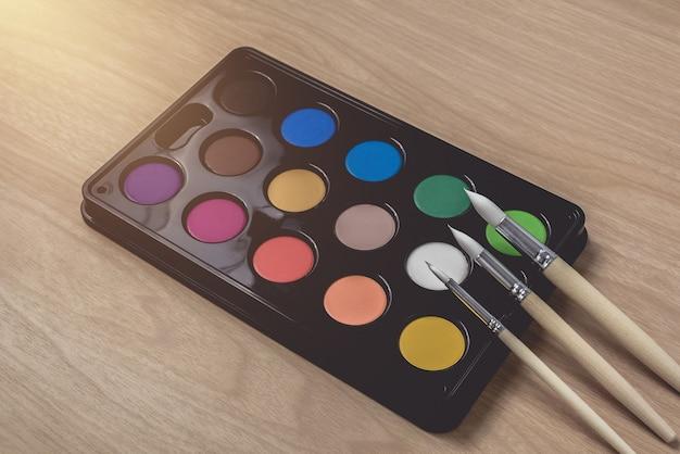 Paleta de pincel e aquarela na mesa de madeira marrom. usando para artes e educação Foto Premium