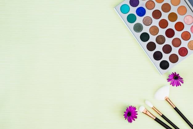 Paleta de sombra colorida com flor roxa e pincéis de maquiagem em fundo de hortelã Foto gratuita