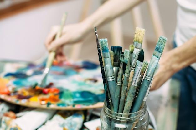 Paleta, pincéis, tintas, foco seletivo em primeiro plano. imagem de fundo. Foto Premium