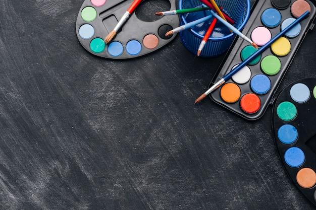 Paletas multicoloridas de tintas em fundo cinza Foto gratuita