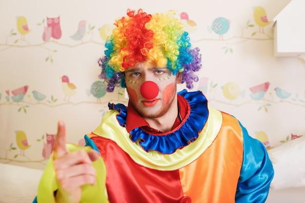Palhaço com fantasia engraçada mostra o dedo. Foto Premium