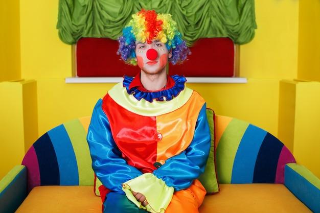 Palhaço sentado no sofá colorido. Foto Premium