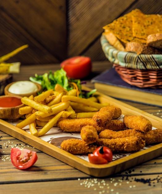 Palitos de frango servidos com batata frita, maionese e ketchup Foto gratuita