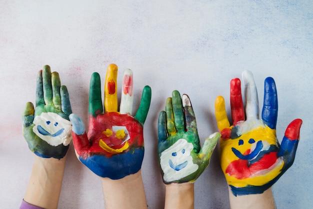 Palmas multicoloridas com rostos sorridentes pintados Foto gratuita