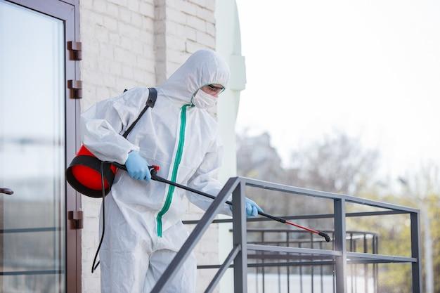 Pandemia de coronavírus. um desinfetante em traje de proteção e máscara pulveriza desinfetantes na sala. Foto gratuita