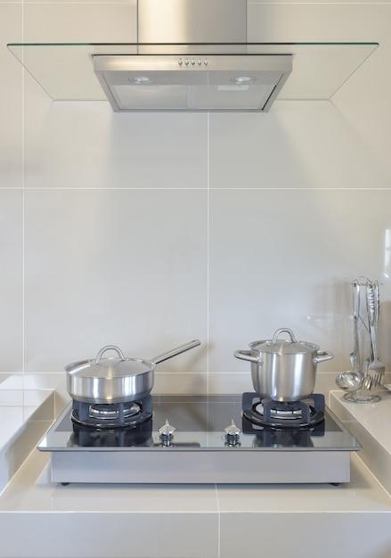 Panela de aço inoxidável em fogão a gás com utensílio na cozinha moderna Foto Premium