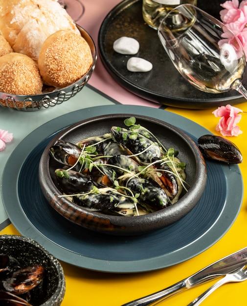Panela de ferro fundido de mexilhões em molho de nata, guarnecida com ervas frescas Foto gratuita