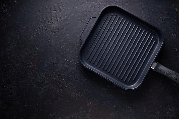 Panela grill preto sobre fundo escuro de pedra vista superior Foto Premium