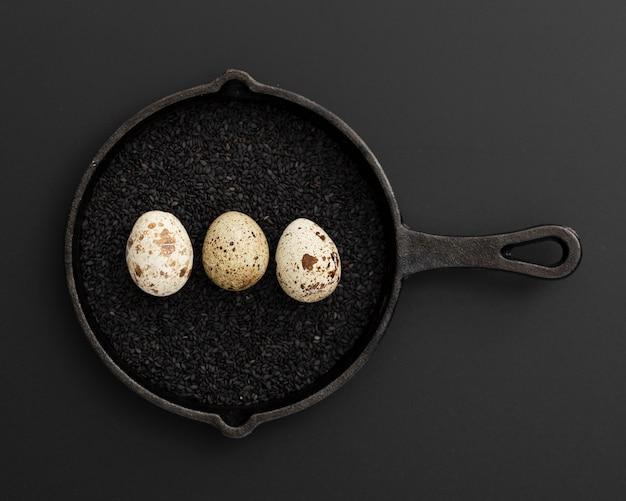 Panela preta com sementes de papoila e ovos Foto gratuita