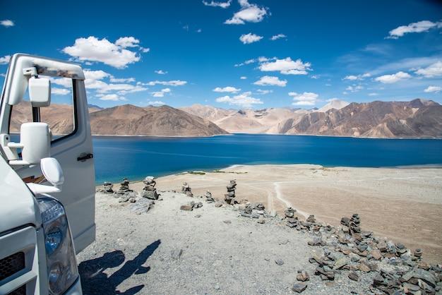 Pangong lago com carro e pilha de pedras Foto Premium