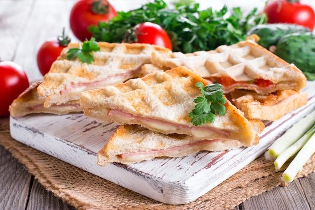 Panini duplo prensado e torrado com presunto e queijo servido em uma mesa de madeira Foto Premium