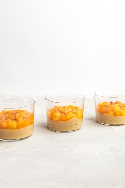 Panna cotta de caramelo, pudim de creme com pêssego e maracujá, mesa branca, cópia espaço Foto Premium