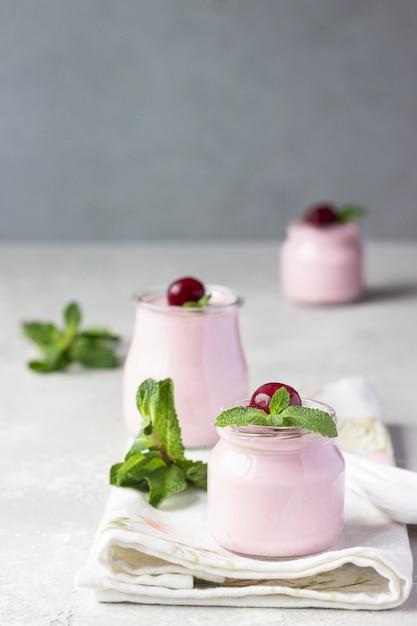 Panna cotta de cereja com cerejas frescas e hortelã em frascos Foto Premium