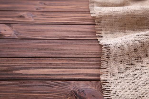 Pano de saco natural no fundo de madeira marrom. lona na mesa de madeira marrom Foto Premium