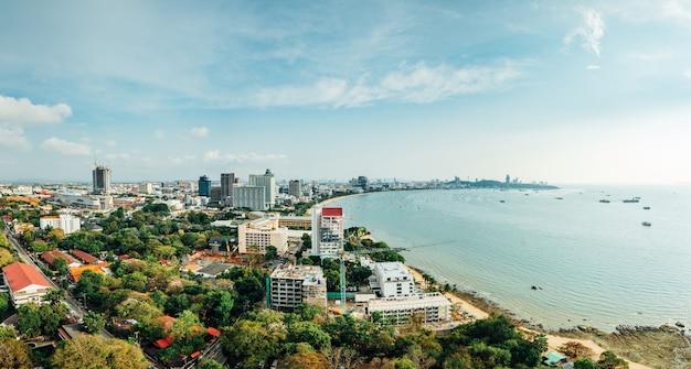 Panorama da arquitetura da cidade com construções e seascape com céu e a nuvem brilhantes da praia de pattaya em chon buri, tailândia. Foto Premium