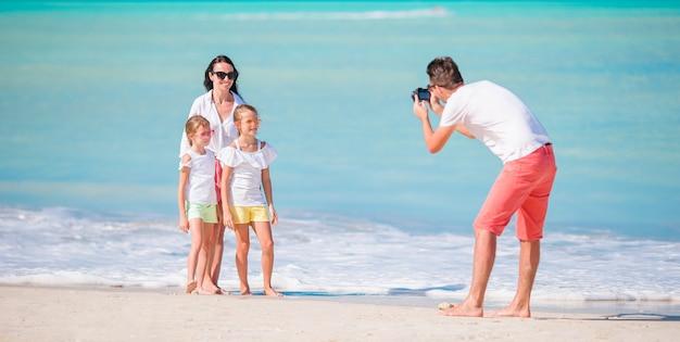 Panorama da família de quatro pessoas que toma uma foto do selfie em seus feriados da praia. férias de praia da família Foto Premium