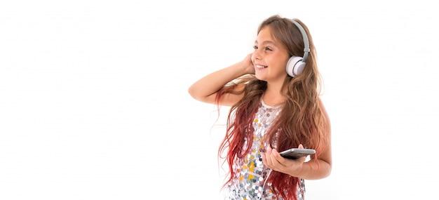 Panorama da menina com grandes fones de ouvido brancos, ouvindo música, tocando o fone de ouvido direito e mantendo preto smartphone isolado Foto Premium