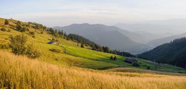 Panorama da paisagem de montanhas, fazenda, celeiros, pilhas de feno Foto Premium