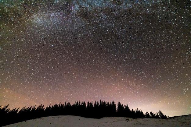 Panorama de paisagem de noite de montanhas de inverno. constelação brilhante da via láctea no céu estrelado azul escuro sobre a floresta de pinheiros de abeto vermelho escuro, brilho suave no horizonte após o pôr do sol. Foto Premium