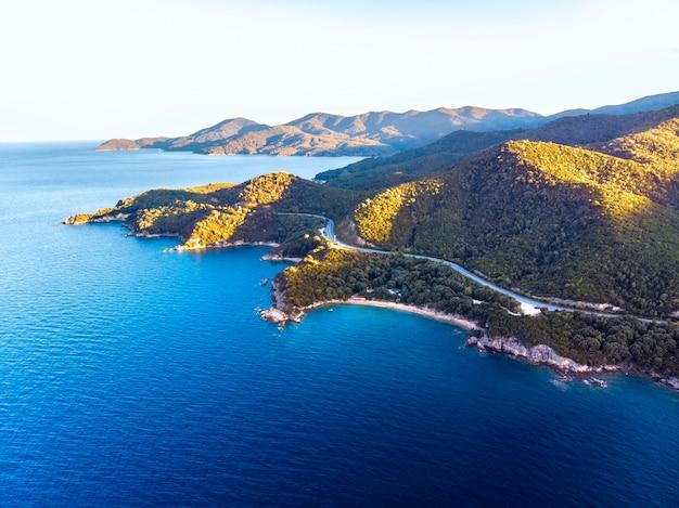 Panorama do pôr do sol em halkidiki com mar azul e montanhas, grécia Foto Premium