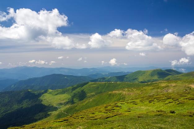 Panorama verde das montanhas sob o céu azul no dia ensolarado brilhante. Foto Premium