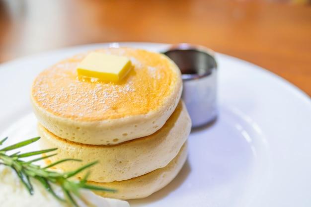 Panqueca com manteiga derretida e xarope no topo Foto gratuita