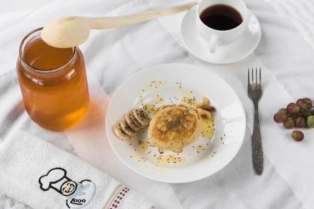 Panqueca; com pote de mel; xícara de café na toalha de mesa Foto gratuita