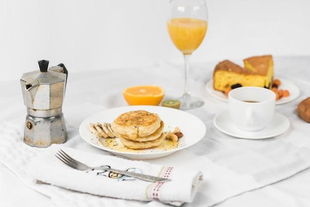 Panqueca; fruta; suco; fatia de bolo e xícara de café na mesa de café da manhã Foto gratuita