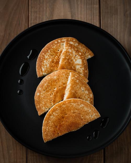 Panquecas americanas ou crepes no prato preto no café da manhã Foto gratuita