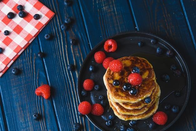 Panquecas com mel e frutas em uma mesa de madeira Foto Premium