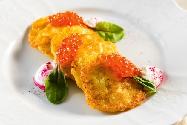 Panquecas de batata com caviar vermelho sob creme de leite e folhas verdes Foto Premium