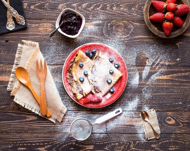 Panquecas de morangos frescos ou crepes com morangos e chocolate Foto Premium