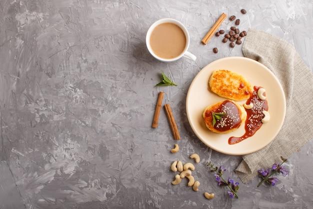 Panquecas de queijo com molho de caramelo em uma placa de cerâmica bege e uma xícara de café em concreto cinza Foto Premium