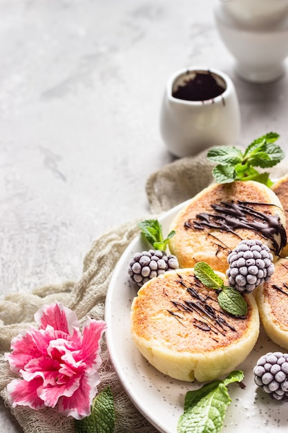 Panquecas de queijo cottage com amoras, chocolate e menta. syrniki. café da manhã gourmet. Foto Premium
