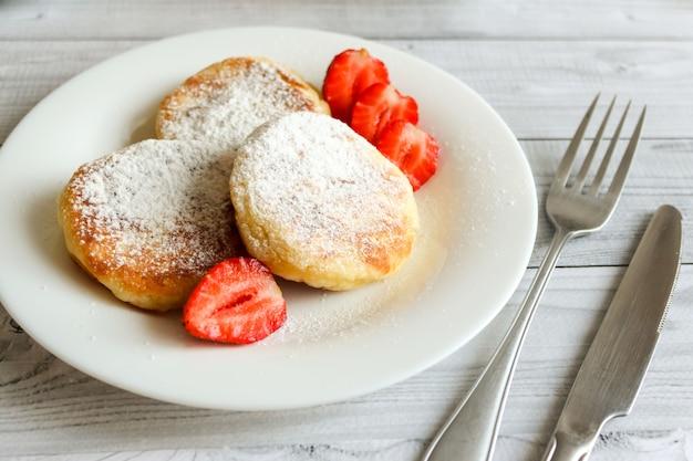 Panquecas de queijo cottage ou syrniki com morangos na chapa branca. Foto Premium