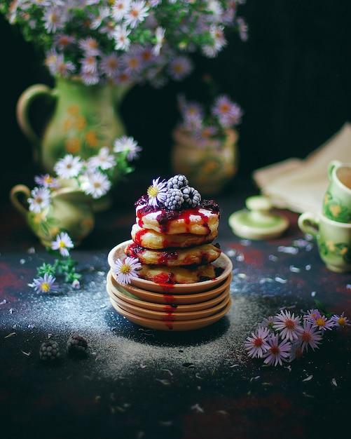 Panquecas de queijo cottage, syrniki, bolinhos de coalhada com frutas congeladas (blackberry) e açúcar em pó em um prato vintage. café da manhã gourmet Foto gratuita