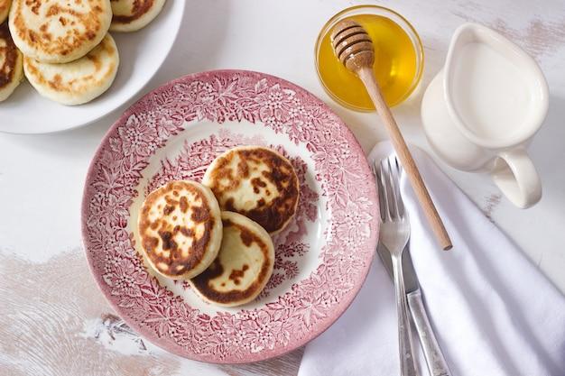 Panquecas de queijo cottage, syrniki caseiro com mel e creme de leite. Foto Premium