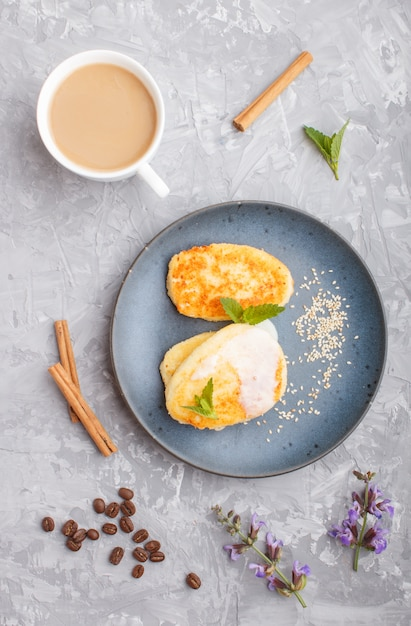 Panquecas de queijo em uma placa de cerâmica azul e uma xícara de café em concreto cinza Foto Premium